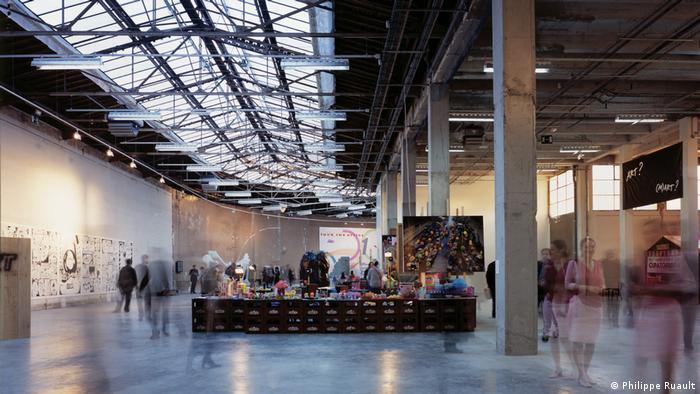Innenraum im Palais de Tokyo: Eine große Ausstellungshalle mit großen Stützen und einer gläsernen Decke.