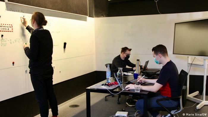 In der Digital Church arbeiten drei Männer an einem Schreibtisch und einem Whiteboard