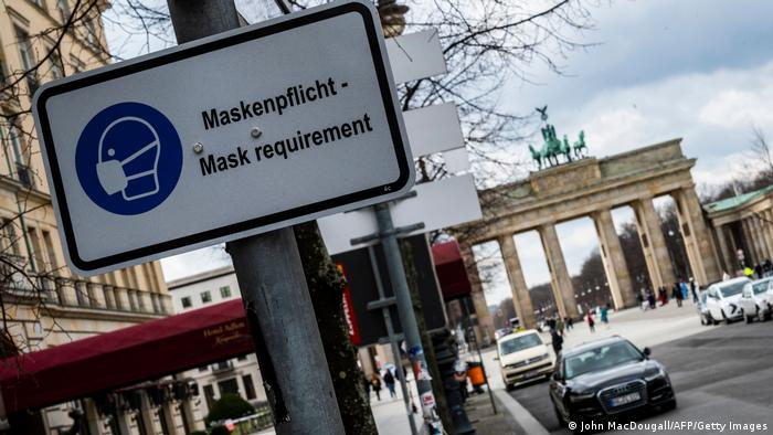 Mask requirement sign in Berlin in front of the Brandenburg Gate