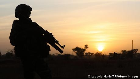 A soldier stands guard at sunset