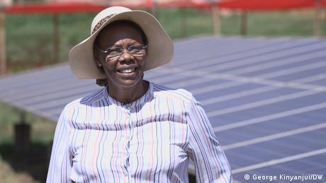 Eine Frau mit einem Hut steht vor einem Solarpanel