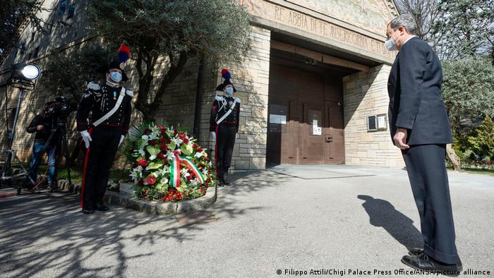 Dois guardas com traje especial e máscaras estão parados ao lado de uma grande coroa de flores com uma fita com as cores da Itália. Em frente, de pé, está o primeiro-ministro, de terno preto e máscara.