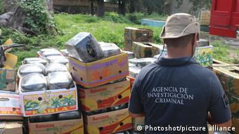 An agent in a shirt of the Criminal Investigation Agency guards stands in front of boxes of marijuana