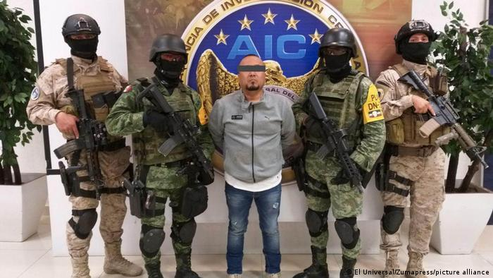 Armed men stand next to a man who is blindfolded