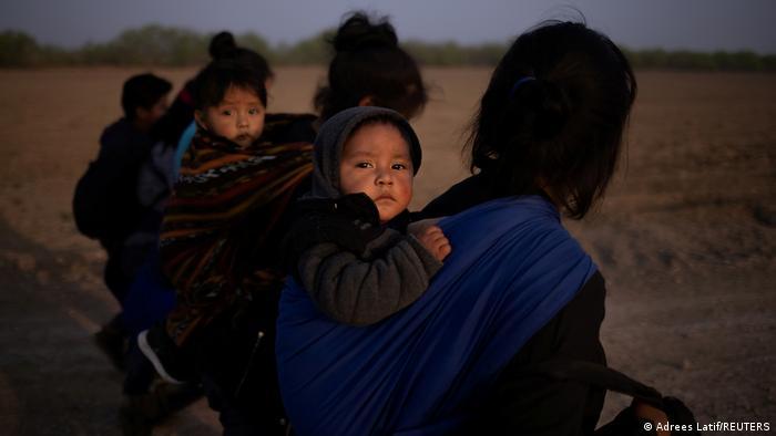 Mujeres cruzando la frontera con sus hijos.