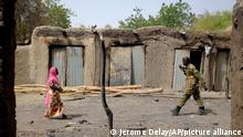 A soldier walks past a woman in Chad