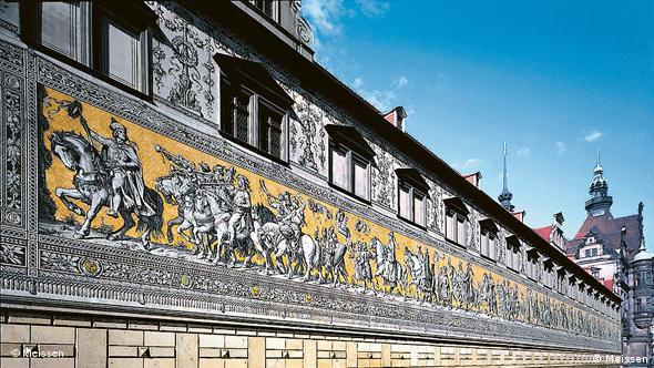 A long wall frieze made out of porcelain is shown on a palace wall in Dresden against a blue sky