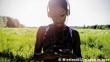 Young athlete in nature, listening music with headphones, holding smartphone model released Symbolfoto PUBLICATIONxINxGERxSUIxAUTxHUNxONLY GIOF04470
