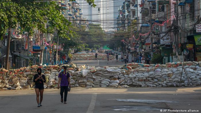 Warga Myanmar berjalan di barikade yang dibuat swadaya