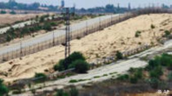 A Palestinian boy in Gaza, with border fortifications in the background