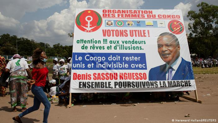 A woman runs past a poster in support of the re-election of the Republic of Congo's incumbent President and presidential candidate Denis Sassou Nguesso, in Brazzaville