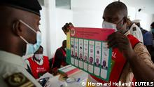 An election agent holds up a list of presidential candidates as security forces cast their ballots ahead of the presidential election which is scheduled on March 21, in Brazzaville, Republic of Congo March 17, 2021. Picture taken March 17, 2021.REUTERS/Hereward Holland