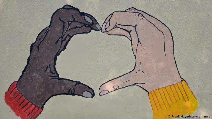 Ilustração de mão negra fazendo gesto de coração com mão branca em símbolo antirracismo.