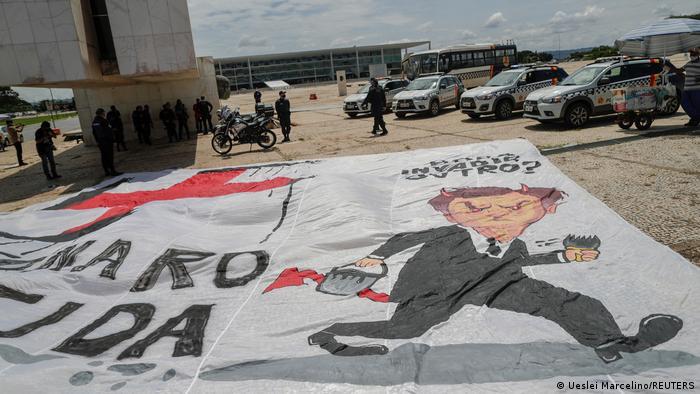 Faixa estendida em frente ao Planalto traz caricatura de Jair Bolsonaro e a frase Bolsonaro genocida