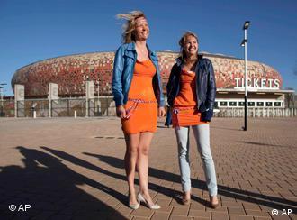 two women wearing orange dresses outside a stadium