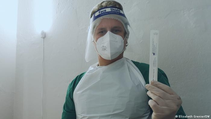 A person wearing medical protective gear shows a COVID test
