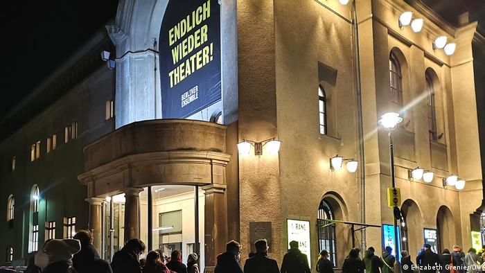 A sign on the Berliner Ensemble theater that reads in German, 'Theater at last!' with people waiting in line