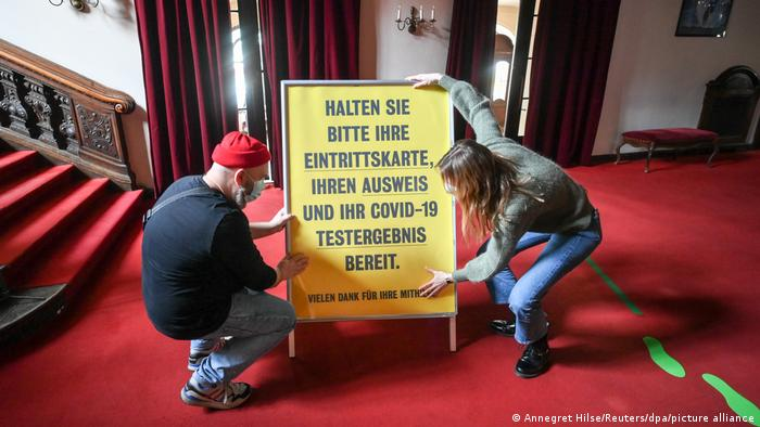 Two people prepare a panel with instructions to get in the Berliner Ensemble theater stating, in German, 'Have your admission ticket, your ID and your COVID test result ready.'