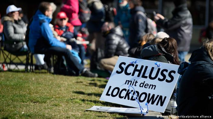 Sign saying 'Finish the lockdown' in front of a group of protesters