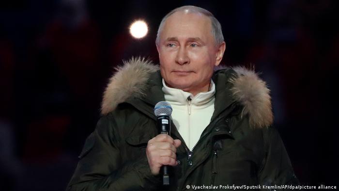 Presidente russo, Vladimir Putin, segurando um microfone.