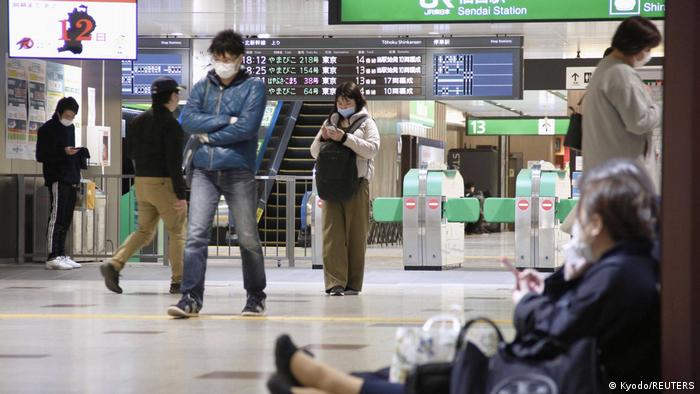 People sit on the floor at a station as train services are suspended following an earthquake in Sendai, Miyagi prefecture