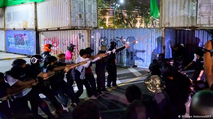 Pro-democracy protesters pull down a shipping container set up as a wall by authorities to block access to the nearby Grand Palace during an anti-government demonstration