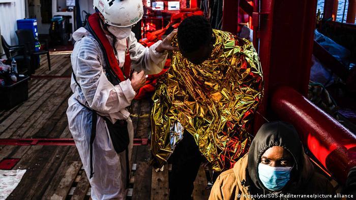 Ein Ocean Viking-Mitarbeiter versorgt einen geretteten Migranten