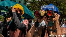 YANGON, MYANMAR - MARCH 20: Anti-coup protesters use binoculars to spot military junta forces on March 20, 2021 in Yangon, Myanmar. Myanmar's military Junta charged deposed de-facto leader Aung San Suu Kyi with accepting bribes and taking illegal payments in gold, as it also continued a brutal crackdown on a nationwide civil disobedience movement in which thousands of people have turned out in continued defiance of tear gas, rubber bullets and live ammunition. Over 180 people have been killed so far according to the U.N. (Photo by Stinger/Getty Images)