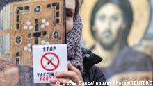 A woman holding an Orthodox religious icon depicting Jesus Christ and a sticker reading Stop mandatory vaccinations attends a protest against mandatory mask wearing and coronavirus disease (COVID-19) vaccination, in Bucharest, Romania March 20, 2021. Inquam Photos/Octav Ganea via REUTERS ATTENTION EDITORS - THIS IMAGE WAS PROVIDED BY A THIRD PARTY. ROMANIA OUT. NO COMMERCIAL OR EDITORIAL SALES IN ROMANIA