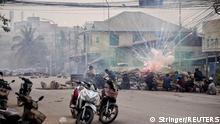 "*** Dieses Bild ist fertig zugeschnitten als Social Media Snack (für Facebook, Twitter, Instagram) im Tableau zu finden: Fach ""Images"" —> Weltspiegel/Bilder des Tages *** 22.03.21 *** Firecrackers explode as protestors take cover behind a barricade during a demonstration against the military coup in Mandalay, Myanmar March 21, 2021. REUTERS/Stringer"