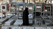 An elderly Iranian woman looks at the graves of soldiers who were killed during 1980-88 Iran-Iraq war, at the Behesht-e-Zahra cemetery just outside Tehran, Iran, Thursday, Macrch 20, 2104, on the eve of the Iranian New Year, or Nowruz. Nowruz which means New Day in Persian, marks the first day of spring and the beginning of the year on the Iranian calendar, which occurs exactly on the Spring Equinox, and usually begins on March 21 or the previous or following day. (AP Photo/Vahid Salemi)