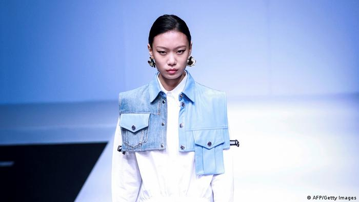 A model wears a denim vest that cuts off below the bust