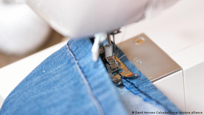 A closeup of a hem being sewn onto a pair of jeans