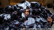A man carrying denim jeans to a local market in Dhaka