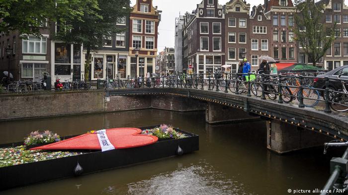 Лодка, украшенная цветами и свечами, в Амстердаме