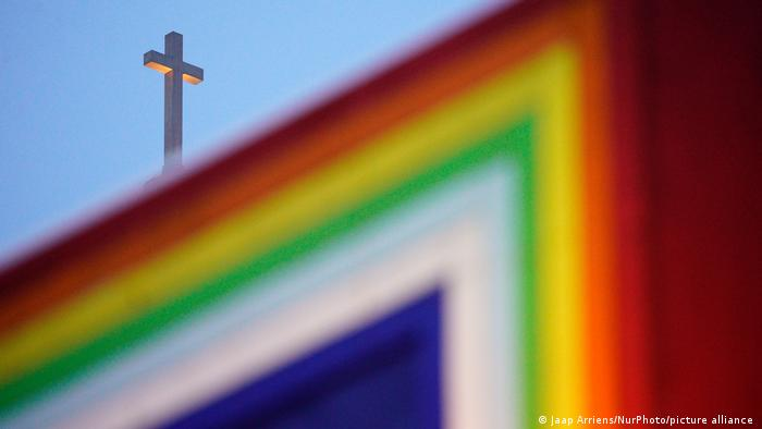 A rainbow colored sculpture and the cross atop a Catholic Church in Warsaw, Poland