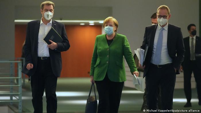 German Chancellor Angela Merkel walks between Berlin Mayor Michael Müller and Bavarian state premier Markus Söder