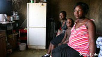 A pregnant South African woman sitting in her kitchen with her two children