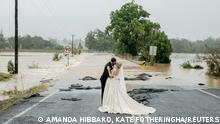 A stranded bride and groom rescued by helicopter on Saturday to get them to the church on time, kiss in front of a flooded bridge that had blocked their five-minute drive into town, in Port Macquarie, Australia in this picture obtained from social media dated March 20, 2021. AMANDA HIBBARD, KATE FOTHERINGHAM /via REUTERS THIS IMAGE HAS BEEN SUPPLIED BY A THIRD PARTY. MANDATORY CREDIT. NO RESALES. NO ARCHIVES. TPX IMAGES OF THE DAY