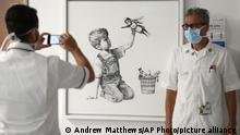 FILE - In this May 7, 2020 file photo, a member of staff has their photograph taken in front of the artwork painted by Banksy during lockdown, entitled 'Game Changer', at Southampton General Hospital in Southampton, England. A Banksy painting honoring Britain's health workers in the coronavirus pandemic has sold for a record 16.8 million pounds ($23.2 million.) Auction house Christie's said Tuesday, March 23, 2021 that proceeds from the sale will be used to fund health organizations and charities across the U.K. (Andrew Matthews/PA via AP, file)
