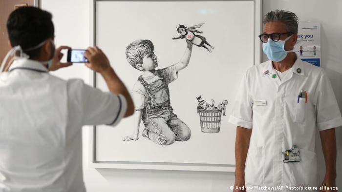 Healthcare workers photograph one another in front of the Banksy painting Game Changer at Southampton General Hospital in England