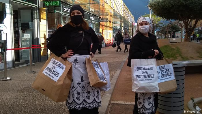 Women hold paper bags with protest slogans in Greek. The women are wearing face masks and traditional Greek dress