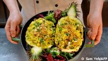 This picture taken on March 10, 2021 shows a restaurant employee holding a dish of pineapple fried rice at the Courtyard by Marriott hotel in Taipei. - A Chinese ban on pineapple imports from Taiwan has sparked a flood of patriotic buying of the fruit and forced restaurants to come up with inventive new menu choices, but it has also left many questioning Taipei's overwhelming economic reliance on its giant neighbour. (Photo by Sam Yeh / AFP) / TO GO WITH AFP STORY TAIWAN-CHINA-POLITICS-FARMS-TRADE-PINEAPPLE,FOCUS BY AMBER WANG