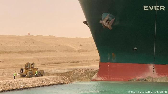Trabajadores junto a un buque portacontenedores.