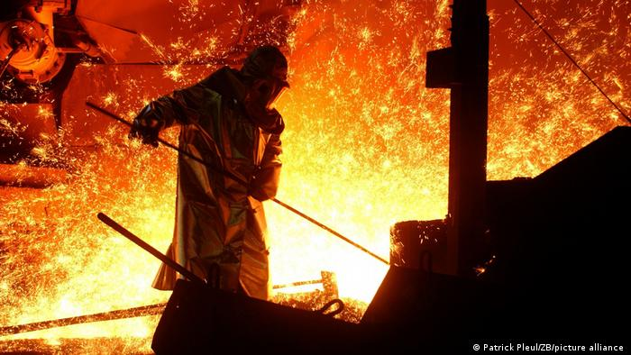 Person wearing protective gear stoking a fire in an ironworks factory, with flames in the background.