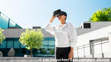 fitness, sport and technology concept - happy smiling young african american woman with virtual reality headset or vr glasses outdoors