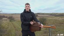 Nathan Evans steht auf einem Feld und klopft auf eine Gitarre