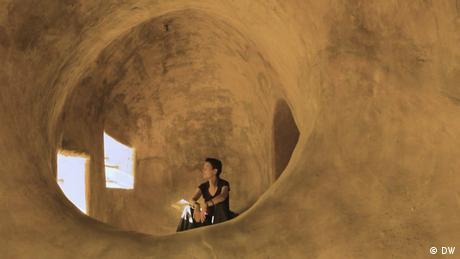 Architektin Anna Heringer sitzt in einem Lehmhaus