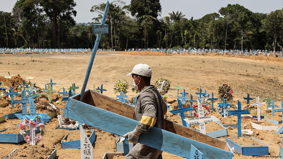 Na nova área da tumba em Manas, um homem carrega uma lápide feita de madeira azul