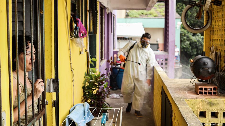 Uma mulher olha pela porta de uma favela enquanto um homem desinfeta a parte externa de seu apartamento